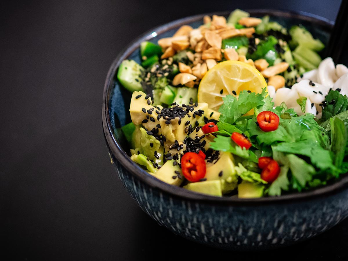 Eine Bowl mit Avocado, Zitrone, Salat, Chili und Nüssen.